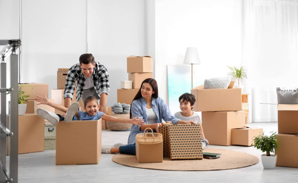 A family with 2 children are packing boxes for moving to a new house
