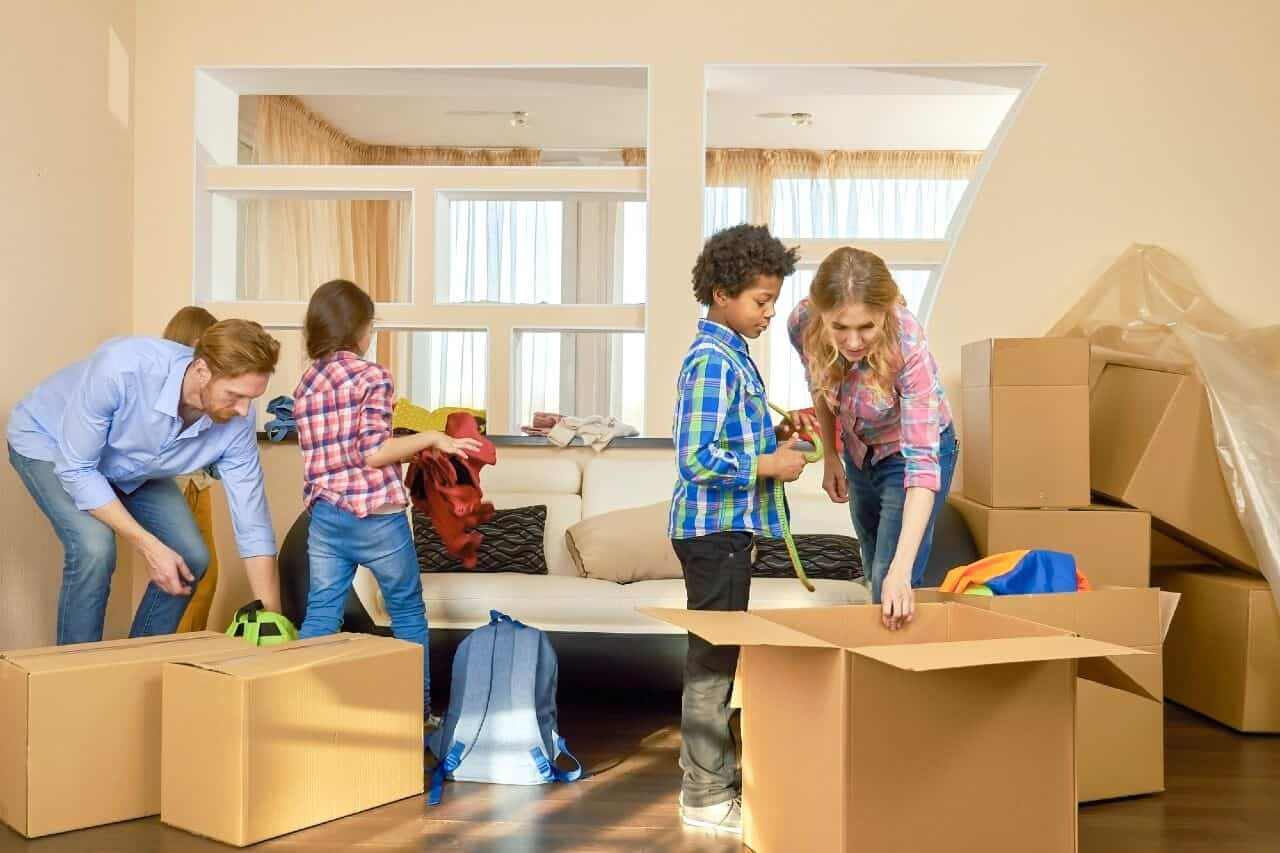 A happy family is packing up removal boxes for moving to the new home