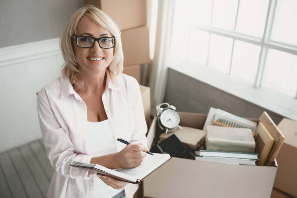 A smiley lady is using the moving checklist to plan for the home move.