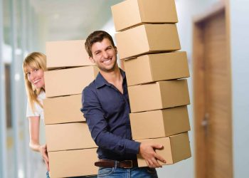 A couples are packing up boxes for storage before moving