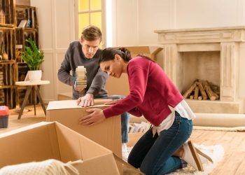 A woman and a man are packing the moving boxes in the living room