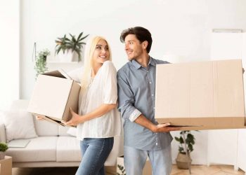 Young couples holding boxes and packing up for moving to the new house