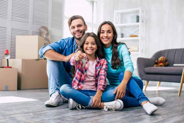 A young family smiling and feel happy for moving home, the girl is holding the new house key